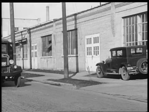 vidéos et rushes de b/w 1928 gm truck driving past warehouse / industrial - 1928