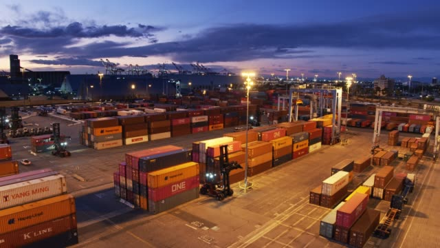 Truck Driving Through Container Port at Night