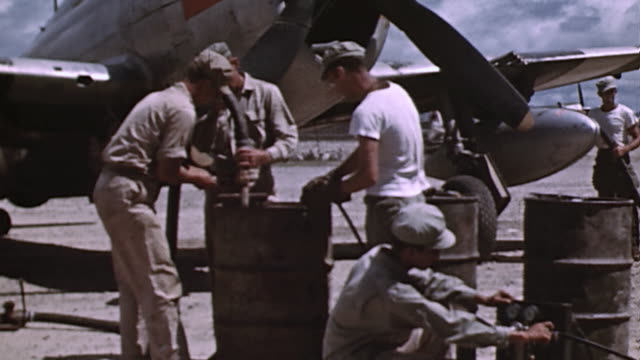 M35 truck dropping off fuel drums on flightline mechanics horsing the drums into position and filling drop tanks beneath P51 Mustang / Mindanao...