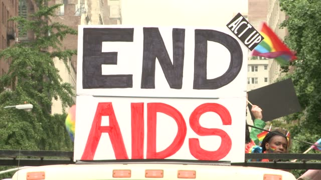 A truck featuring the messages 'END AIDS' and 'FIND A CURE' / WKTU FM radio's float also appears / Various shots of the crowd as the parade enters...