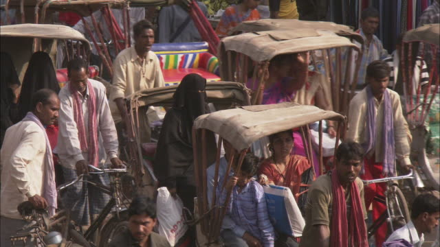 A truck follows behind rickshaws on a congested road in India.