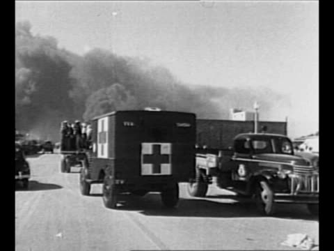 truck full of responders drives away from camera, toward black smoke of texas city fires, followed by red cross ambulance / vehicle with responders... - red cross stock videos & royalty-free footage