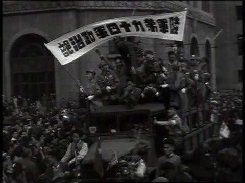 truck full of soldiers holding banner / young soldiers waving little flags / doctors and nurses in white on bicycles / the procession through crowded...