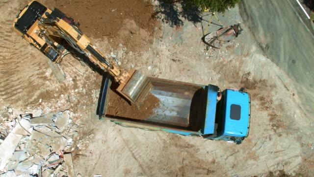 vídeos de stock, filmes e b-roll de antena caminhão indo para trás em direção a escavadeira carregando-a com solo - meio de transporte