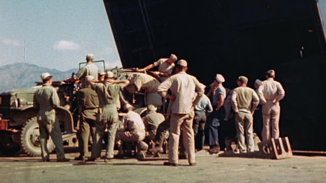 vidéos et rushes de ws truck hauling two trailers one open driving from lst bow doors to wharf / corsica france - 1944