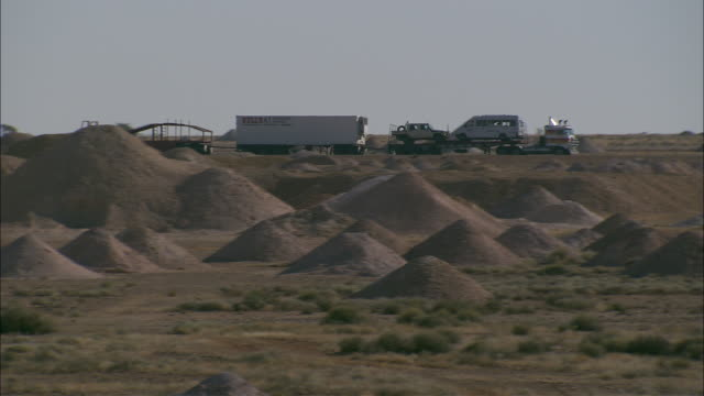 a truck hauls a large load past dirt mounds at the coober pedy mines. - coober pedy stock videos & royalty-free footage