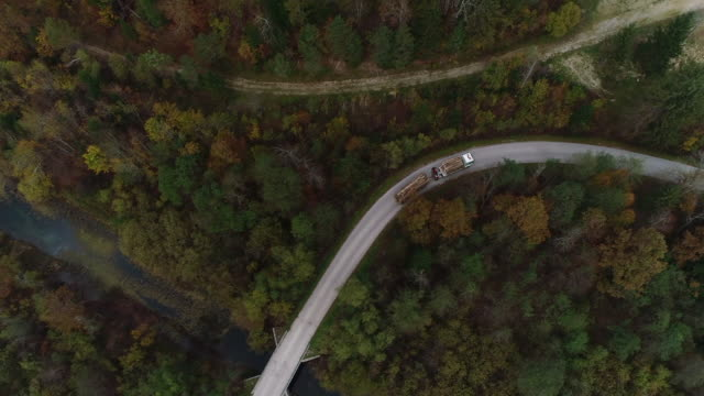 vídeos de stock e filmes b-roll de truck loaded with wood driving on country road from drone point of view - madeira material