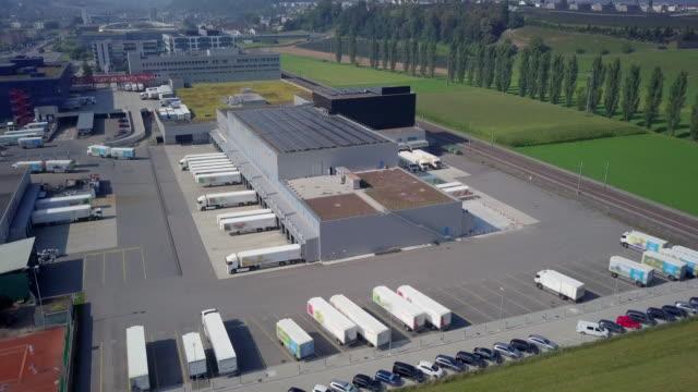 truck logistics center und solar field außerhalb der stadt luzern in der schweiz. - groß stock-videos und b-roll-filmmaterial