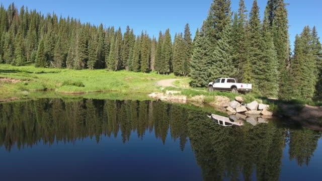 vídeos de stock e filmes b-roll de truck low to high mountain reveal beautiful reflection,rocky mountains reveal fall colors lake reflection, off road, rzr wildlife, foliage short aerial, 4k, 32s, 5of102, stock video sale - drone discoveries - drone aerial view - reflection