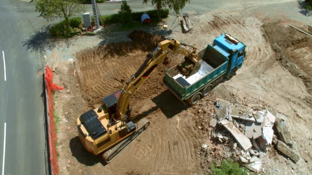 aerial truck moving backwards so the excavator can load it with soil at the sunny building site - construction equipment stock videos & royalty-free footage