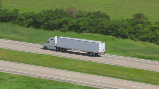 WS TS ZO AERIAL POV Truck moving on road in farmland / Iowa, United States