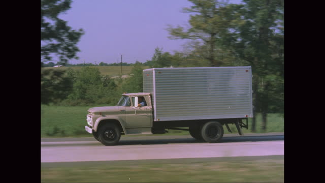 ws ts truck moving on road / united states - 1960 stock-videos und b-roll-filmmaterial