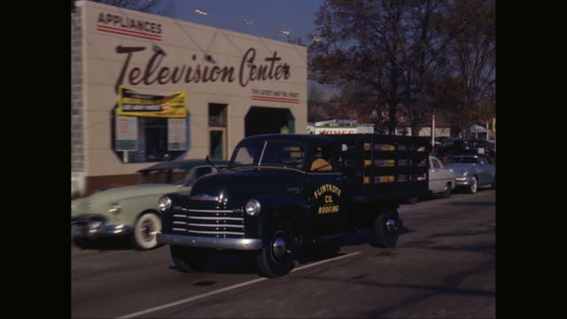 ws pov truck moving on road with shops and commercial signs in background / united states - telephone line stock videos and b-roll footage