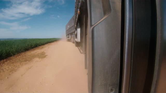 vídeos de stock, filmes e b-roll de truck on dry ground road between fields, brazil - caminhão