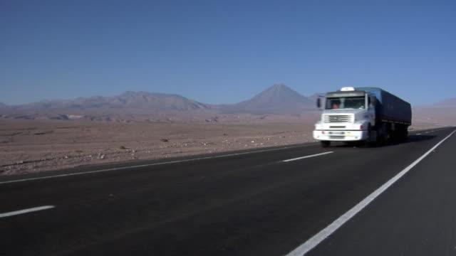 ms truck on road crossing desert landscape, volcano in background, san pedro de atacama, el loa, chile - san pedro de atacama stock videos & royalty-free footage