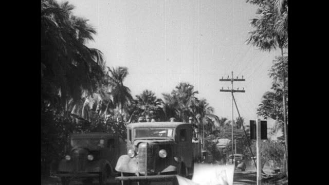 truck on road in rural area, japanese soldiers with propaganda papers / filipino people, children, mother holding child, watching / loudspeaker with... - pacific war video stock e b–roll