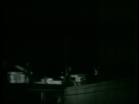 dramatization night truck on road investigator peters lindsey reporting in men loading boxes from truck onto boat ms commander stephen s yeandle pj1... - 密輸点の映像素材/bロール