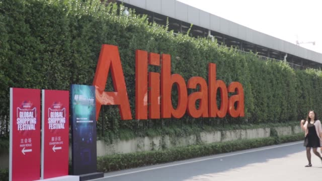 A truck passes a sign for Alibaba Group Holding Ltd displayed at the company's headquarters in Hangzhou China on Tuesday Oct 13 A car passes signage...