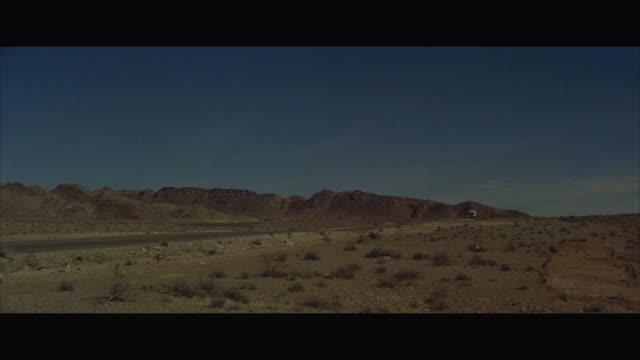 vídeos y material grabado en eventos de stock de ws pov truck passing through road in desert hills - 1960