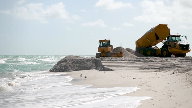 truck prepares to dump sand along the beach as the u.s. army corps of engineers works on widening parts of the beach on january 14, 2020 in miami... - sand stock videos & royalty-free footage