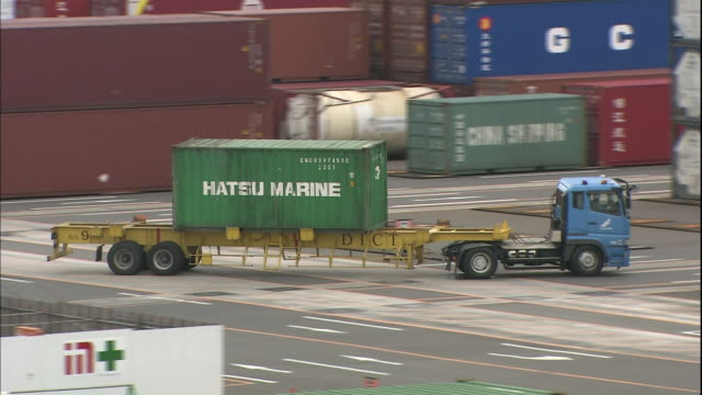 a truck pulls a trailer through a container yard in the osaka south port in japan. - 貨物用コンテナ点の映像素材/bロール