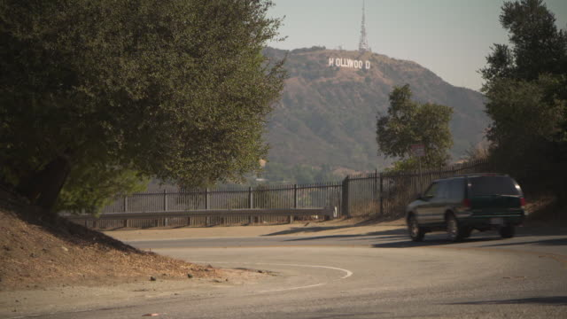 a truck rounds a corner on a road overlooking the hollywood sign on mount lee los angeles california usa fkax253n clip taken from programme rushes... - ecke eines objekts stock-videos und b-roll-filmmaterial
