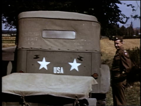 vidéos et rushes de truck standing in road / soldier climbing into truck - 1945