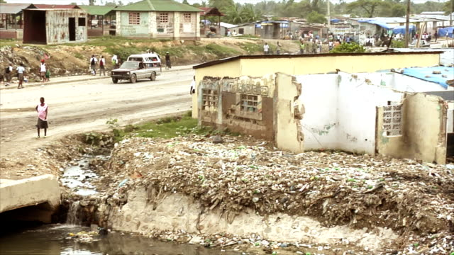 truck taxi driving across trash filled stream - haiti stock videos & royalty-free footage