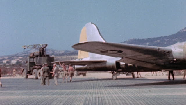 Truck towing B17 Flying Fortress with flat tire as enlisted men assist and flight crew wearing Mae Wests posing with ground crew / Calvi Corsica...