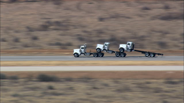 truck towing two trucks on route 82  - aerial view - texas,  baylor county,  united states - towing stock videos & royalty-free footage
