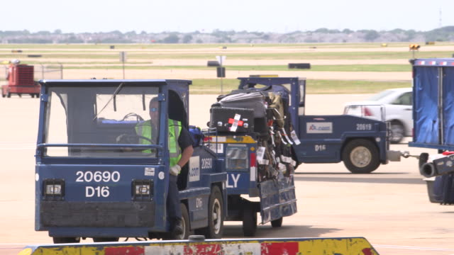 Truck tows passenger baggage from aircraft to terminal with airplane in background/DFW International Airport, Dallas-Fort Worth, Texas, USA