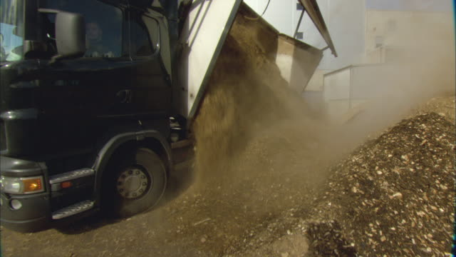 ws pan truck unloading pile of woodchips at biomass plant / vaxjo, sweden - vaxjo stock videos & royalty-free footage