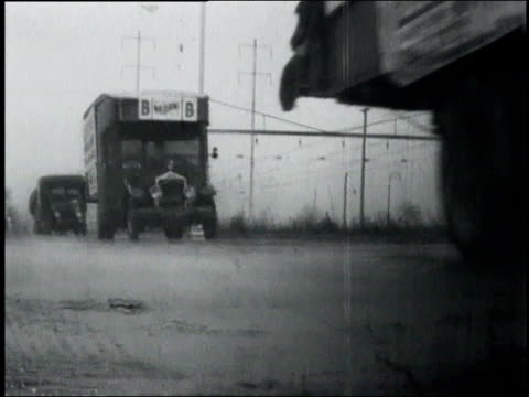 truck wheels rolling / convoy of large trucks driving / the shoes of men marching / two men marching / the capital building / people holding up signs... - 1932 stock-videos und b-roll-filmmaterial