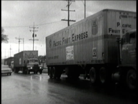 truck with sign reading city in action through civil defense / trucks driving through the street / truck backing into dock - 1960 stock-videos und b-roll-filmmaterial