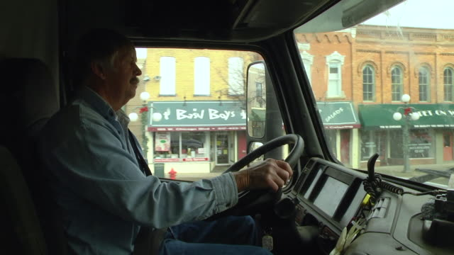 vídeos y material grabado en eventos de stock de ms pov slo mo truckers driving truck for small businesses through city / chelsea, michigan - camionero