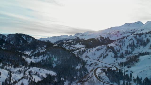 トラック バック空中ドローン赤山雪道のショット (道路: 百万ドル高速道路) サンファン山脈 (赤峠近くのロッキー山脈) の森の木々 に囲まれた冬のユーレイ、コロラド州の外で - ユアレイ市点の映像素材/bロール