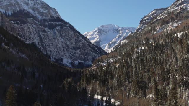 雪に覆われた谷のサンファン山脈 (ロッキー山脈) 青空の下でユーレイ、コロラド州の外の雪を頂いた山運送戻って空中ドローン ショット - ユアレイ市点の映像素材/bロール
