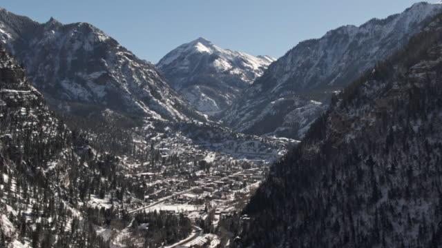 木の雪に覆われた森林とサンファン山脈 (ロッキー山脈) 青空の下でコロラド州ユーレイの上の雪を頂いた山のトラック運送戻って空中ドローン ショット - ユアレイ市点の映像素材/bロール