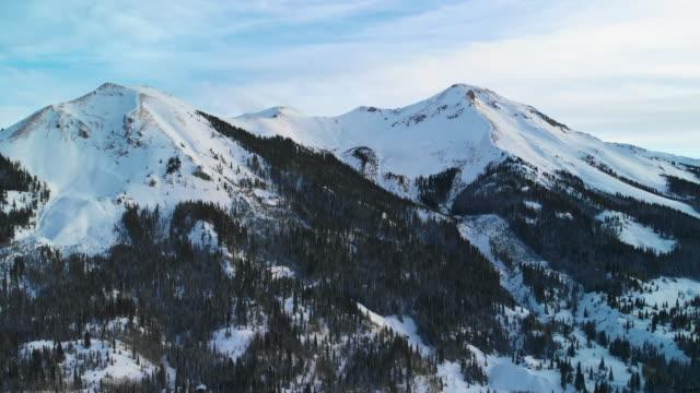 冬の森の木々 に囲まれたコロラド州ユーレイ外サン フアン山 (赤峠近くのロッキー山脈) の雪に覆われた山頂のトラック バック空中ドローン ショット - ユアレイ市点の映像素材/bロール