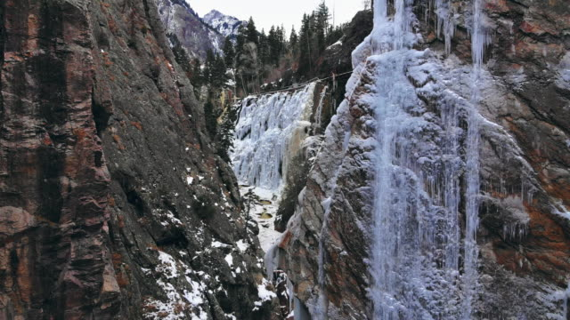 trucking back drone shot of a narrow mountain canyon with snow, a stream, a wall of icicles (ice park), and a frozen waterfall in ouray, colorado - narrow stock videos & royalty-free footage