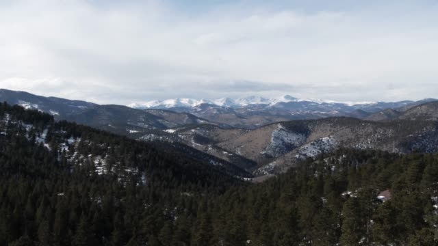 trucking backward aerial drone shot of snowcapped mountain peaks of the rocky mountains in colorado near denver on a sunny winter day - rocky mountains north america stock videos & royalty-free footage