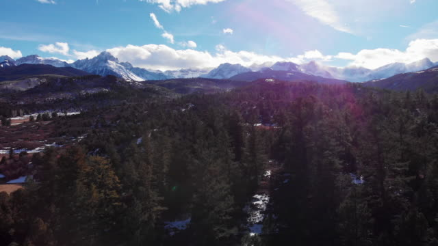 trucking forward aerial drone shot of a forest and snowy peaks of the san juan mountains (rocky mountains) outside telluride, colorado on a bright, winter's day - montagne rocciose video stock e b–roll