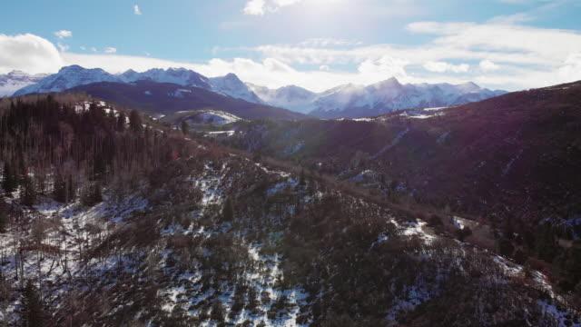 森のサンファン山脈 (ロッキー山脈) テルライド、コロラド州、冬の日を明るく、外の雪に覆われたピーク運送前方空中ドローン ショット - ユアレイ市点の映像素材/bロール