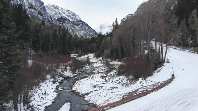 サンファン山脈 (ロッキー山脈) の森の木々 に囲まれた冬のユーレイ、コロラド州の外で流れるストリームで雪峠 (道) の運送前方空中ドローン ショット - ユアレイ市点の映像素材/bロール