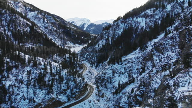 赤山雪道の前方空中ドローン ショットをトラック輸送 (道路: 百万ドル高速道路) サンファン山脈 (ロッキー山脈) の森の木々 に囲まれた冬のユーレイ、コロラド州の外で - ユアレイ市点の映像素材/bロール