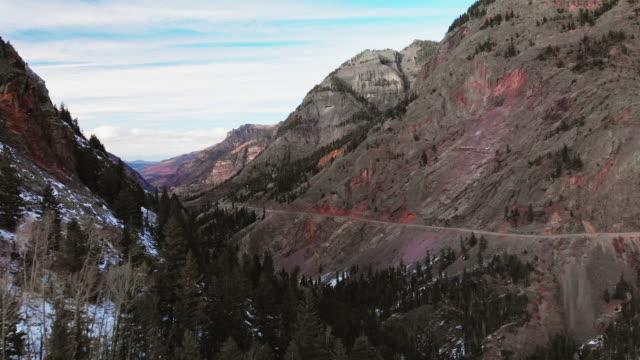 トラックの前方空中ドローン ショットの赤峠 (道路: 百万ドル高速道路) 曇り空の下でコロラド州ユーレイ外フォレストおよびサンファン山脈 (ロッキー山脈) の雪の光に散布と山頂に近い - ユアレイ市点の映像素材/bロール