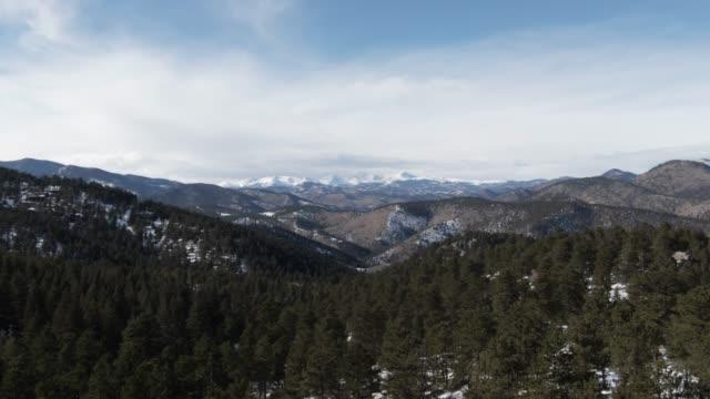 camioning forward drone drone colpo di neve innevato cime montuose delle montagne rocciose in colorado vicino denver in una soleggiata giornata invernale - sunny video stock e b–roll
