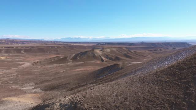 デザート ヒルズとメサの距離のサンファン山脈 (ロッキー山脈) と西部コロラド州のドミンゲス エスカランテ国立保護地域外の運送前方空中ドローン ショット - ユアレイ市点の映像素材/bロール