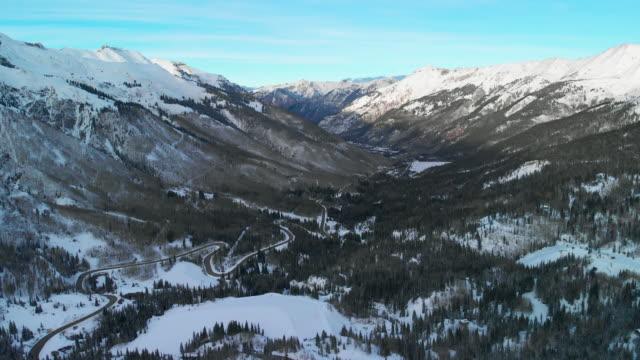 赤山雪道の空中ドローン ショットを前方/傾斜トラック輸送 (道路: 百万ドル高速道路) サンファン山脈 (ロッキー山脈) の森の木々 に囲まれた冬のユーレイ、コロラド州の外にある谷に - ユアレイ市点の映像素材/bロール