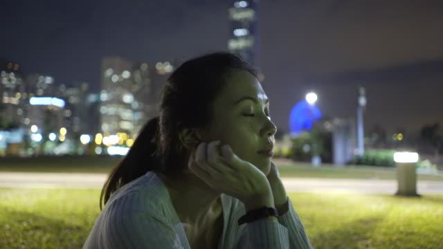 Trucking shot, Hong Kong skyline over woman in park
